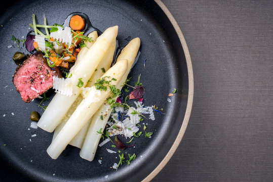 Modern Style classic white asparagus with barbecue dry aged sliced beef fillet and vegetable served as top view on a minimalistic design plate