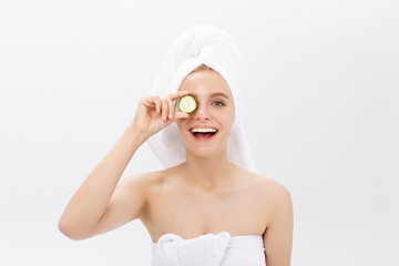 Young beautiful nude girl smiling hiding eyes behind cucumber slices over white background. Beauty skincare and cosmetology