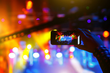 Young people shoot photo or video of a concert on smartphone.