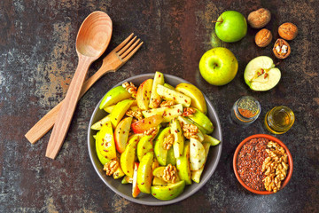 Appetizing apple salad. Vegan bowl of apple salad with walnuts. Healthy autumn salad with apples, nuts, flax seeds and spices.