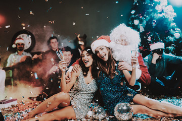 Two Young Women with Santa Claus on New Year Party