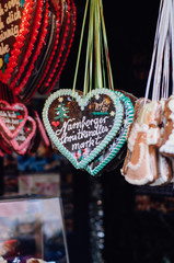 Traditional German Gingerbread heart, so called Lebkuchenkerz, a baked cookie with sugar icing, hanging at stall at Nuremberg Christmas market sold as gift for loved ones or souvenir