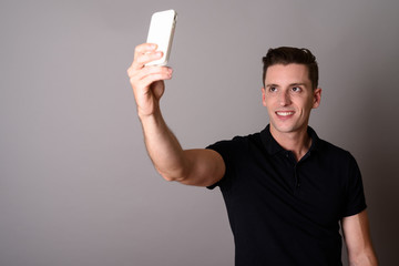 Young handsome man using mobile phone to take selfie