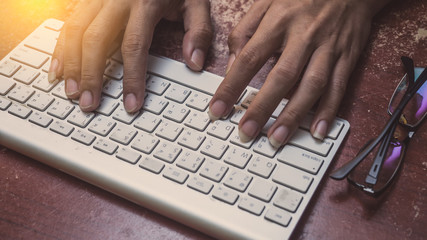 Wall Mural - Close up of a man hands working with a keyboard in office