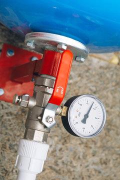 expansion tank with pressure gauge in boiler room