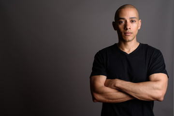Handsome bald man wearing black shirt with arms crossed