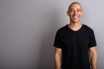 Handsome bald man smiling and looking at camera Wall mural
