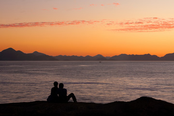 Romantic couple silhouette at sunrise by the sea