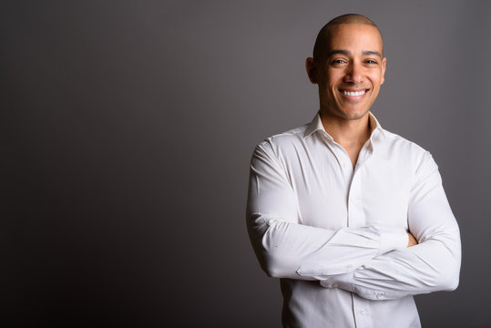 Handsome bald businessman smiling with arms crossed