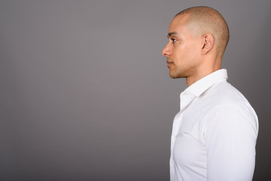 Profile view of handsome bald businessman against gray background