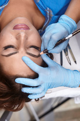 microblading, woman drawing with pencil eyebrow shape, elevated view.