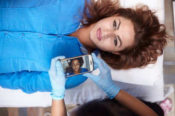 microblading, woman pre-visualizing, checking eyebrow shape on smartphone app. elevated view.