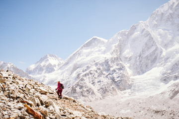A woman hikes alongside the Khumbu Glacier in the Himalayas