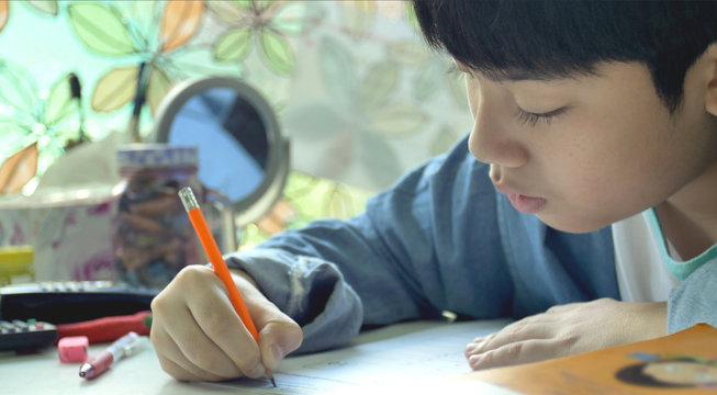 Asian child doing your homework at home.
