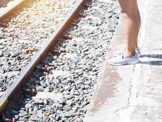 woman tourist leg standing and waiting for the train at platform