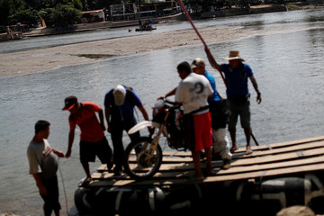 People use rafts to cross the Mexico-Guatemala border across the Suchiate river, in Ciudad Hidalgo