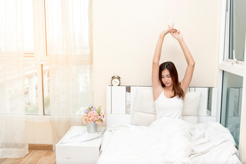 Lazy woman just wake up holding both arms in the morning