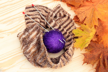 a ball of wool and around a scarf. two knitting needles stuck in them on a wooden background. There are yellow maple leaves without attention