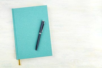 Obraz A photo of a teal blue journal with a pen, an elegant notebook or planner, shot from above with copy space - fototapety do salonu