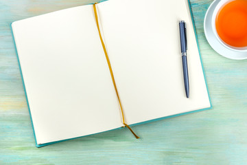 An overhead photo of an open journal notebook with a pen and a cup of tea, shot from the top, a diary on a teal blue background with copy space