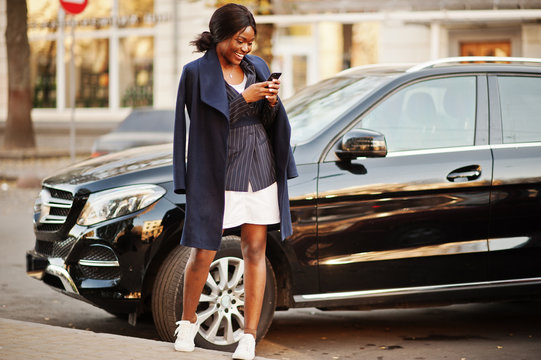 Success stylish african american woman in coat against black business suv car looking at phone.