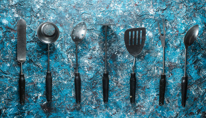 Retro metal cooking tool set on a blue concrete background.