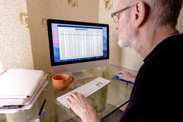 Mature man with beard working on a spreadsheet on computer. Folders with files, pens and an orange cup are put on the table