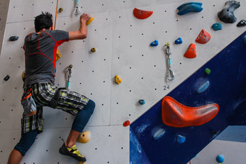 Young man wearing colorful sport clothing climbing on an advanced climbing wall indoors - Pictures taken in a climbing center in Quebec, Canada.