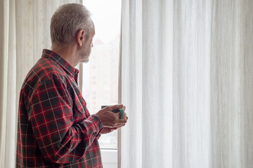 Mature man drinking his coffee in a green cup, while he is looking out of the window
