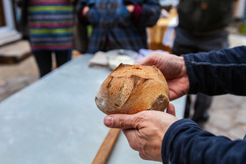 Man is holding a small loaf of bread that just came out of an outdoor bread oven, with people around looking - Pictures taken during a bread and pizza making workshop