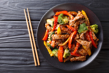 delicious Asian teriyaki beef with red and yellow bell peppers, broccoli and sesame seeds close-up on a plate. horizontal top view
