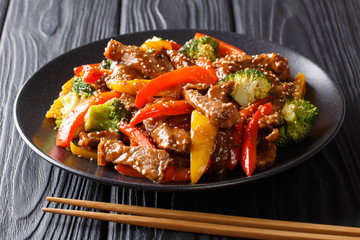 Asian food: teriyaki beef with red and yellow bell peppers, broccoli and sesame seeds close-up on a plate. horizontal