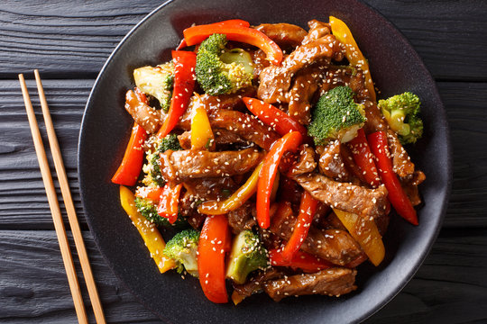 Asian teriyaki beef with bell pepper, broccoli and sesame close-up on a plate. horizontal top view