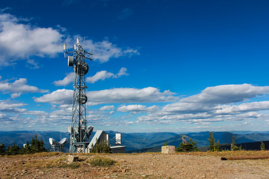 GPS Tower on the top of a mountain in Creston Valley, Kootenays, BC - Pictured on a beautiful summer day with small scattered cumulus clouds around