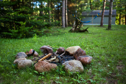 Campfire pit on green lawn with a hammock hanging in the background - 1/2 - Wide angle picture showing a big part of the backyard