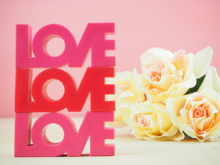Love red and beautiful flowers on wooden floor and pink background. Valentine's Day Background.