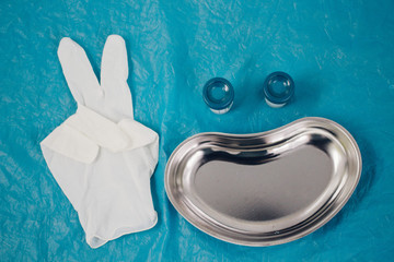 medical tray, disposable gloves showing the peace sign, jars for taking biomaterial lined in the form of a smiling face. health, longevity,