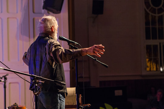 Old man is storytelling in an old church during a spoken word community festival - As seen from the back, with a lateral view
