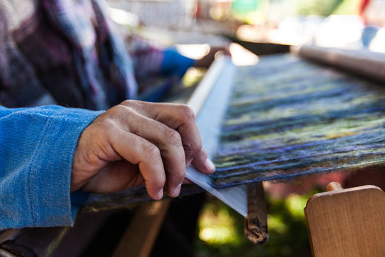 Man is weaving very fancy multi colored wool using a wooden loom - 3/6 - Closeup picture showing the different colors of the wool