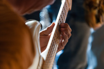 Guitarist is playing a solo on his white electric guitar in a pub - Closeup picture with a blurry saxophonist in the background