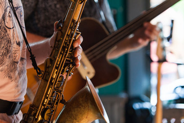 Tenor Saxophone player is playing a jazz solo in a pub - Closeup picture with a blurry fretless bassist playing in the background
