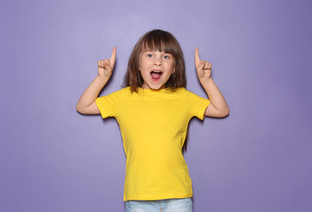 Little girl in t-shirt pointing at something on color background
