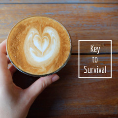 Inspirational motivation quote about coffee on hot cup of latte with hand holding