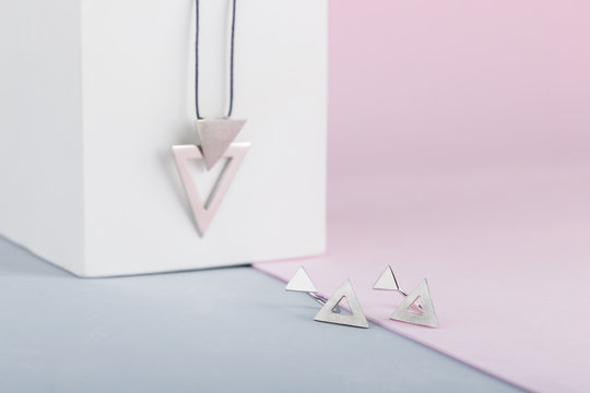 Modern minimalist Triangle shape silver earring on pink background