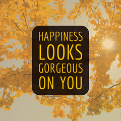 """Inspirational motivation quote """"Happiness looks gorgeous on you"""" on yellow leaves tree background"""