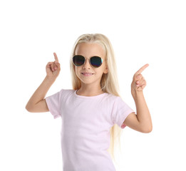 Cute little girl in t-shirt pointing at something on white background