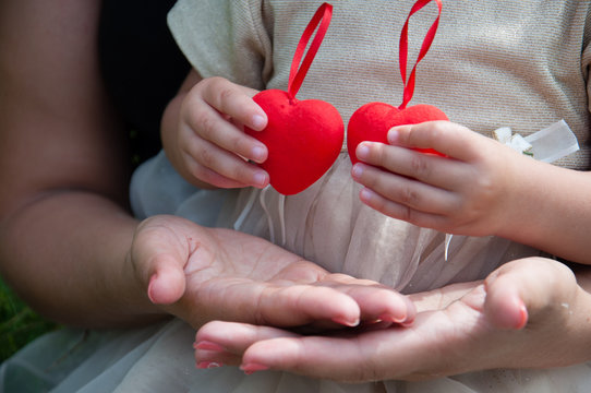 Red hearts in children's hands. The girl is holding red hearts. Concept family, happiness, love, valentine's day
