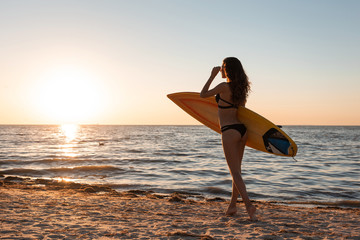 Slim dark-haired girl in a swimsuit walks on the sandy beach near the sea on the sunset and holds a surfboard