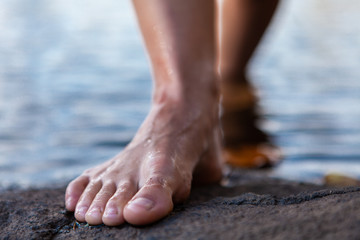 Young woman walking out of the water bare feet on a rock - Closeup picture taken from a low angle showing the focus on the toes