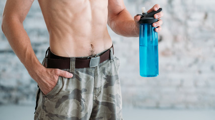 hydration while exercising. man holding water bottle. healthy lifestyle and fitness tips. cropped image of muscled male torso.